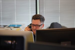 Man with glasses on phone call at desk